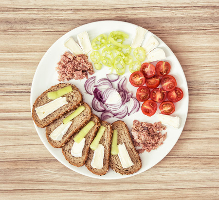 multi grain sandwich: Sliced whole wheat bread with cheese, paprika, tuna, onion and cherry tomatoes on the plate. Food theme.