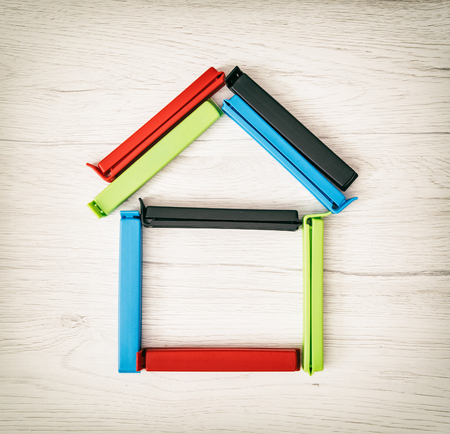 symbolic: Little house shape of colorful bag clips on the wooden background. Symbolic object. Stock Photo