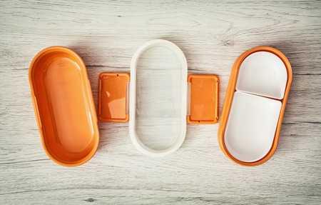 food storage: Orange folding plastic box for food storage on the wooden background.