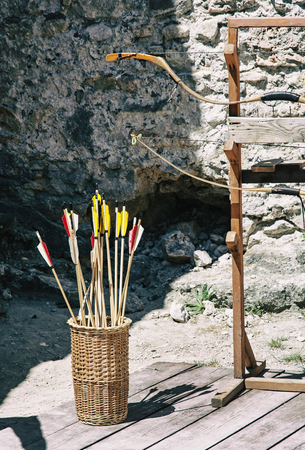 solter�a: Vintage bow and arrows with ruins wall background. Outdoor activity.