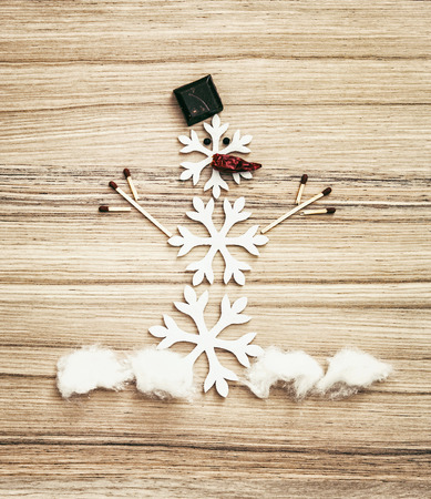 cotton wool: Beautiful snowman made of snow flakes, matches, chocolate, cotton wool and chili peppers on the wooden background. Symbol of white winter. Stock Photo