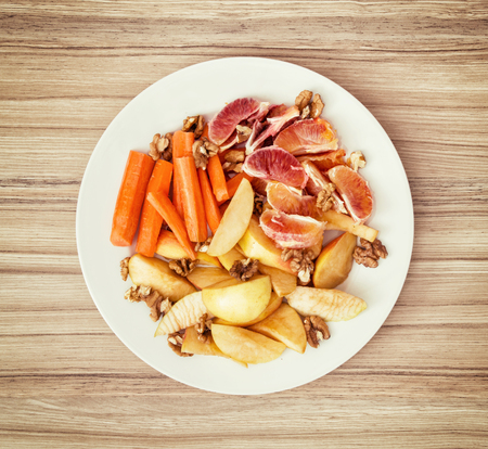 fruit plate: Sliced carrots, apple, grapefruit, oranges and walnuts on a white plate. Fruit theme. Healthy food.