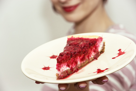 provocative food: Beautiful joyful woman posing with the piece of cheesecake with raspberries. Sweet food theme. Stock Photo