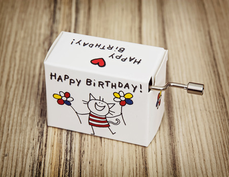Music box with funny title happy birthday on the wooden background.