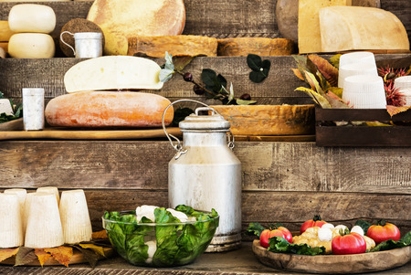 Dairy products and vegetables on the wooden background. Grocery shop.