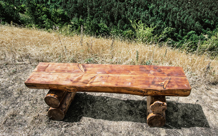 wooden bench: Wooden bench serving to rest during the hiking. Travelling theme. Stock Photo