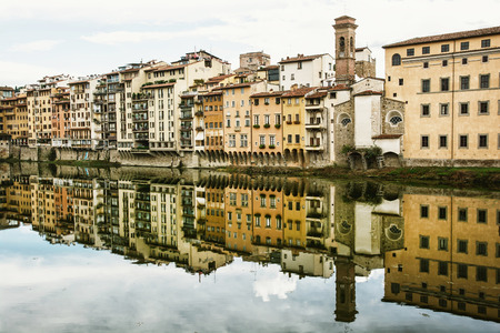 oppositional: Old buildings with bell tower mirrored in the river Arno, Florence, Tuscany, Italy. Urban scene.