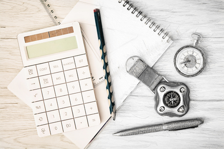 pocket watch: Compass, pocket watch, calculator, notepad, ruler, pen and pencil on the wooden background. Photography and drawing.