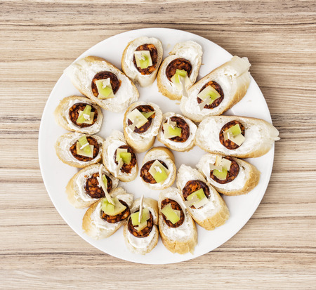 refreshments: Tasty canapes with butter, sausage, cheese and paprika. Food theme. Refreshments for guests.