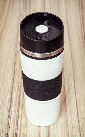 kitchen equipment: Coffee thermal mug on the wooden background. Kitchen equipment.