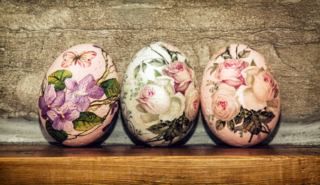 easteregg: Three Easter eggs stacked on the wooden base. Easter holiday. Symbol of springtime.