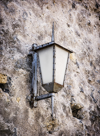 architectural lighting design: Vintage street lamp hanging on the old wall. Lighting equipment.