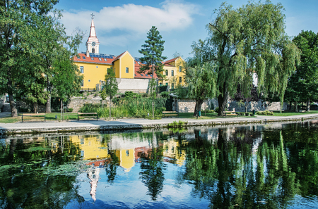 mirroring: Church and convent in Tapolca is mirroring in the water level of the lake. Hungary, central Europe. Architecture and nature.