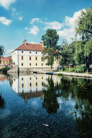 golden fish: Mill house is mirroring in the water level of the lake, Tapolca, Hungary, central Europe. Golden fish.