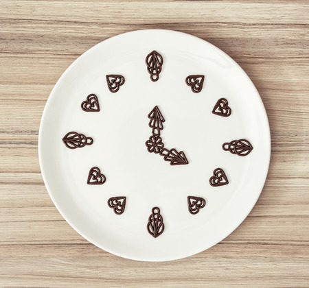 piped: Dark chocolate garnishes in the shape of the clock. Symbolic food.
