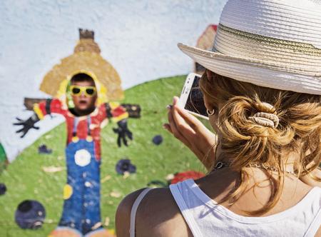 solter�a: mujer cauc�sica joven toma foto de su hijo en el parque de la familia. Actividad al aire libre.