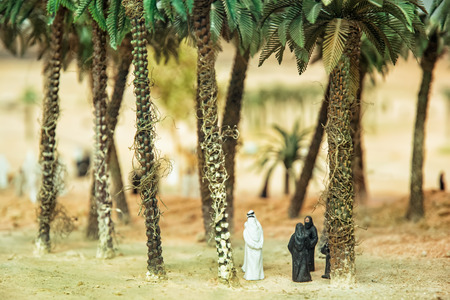 desert oasis: Little figurines of Arabs in the desert oasis under the palm trees. Artistic symbolic objects. Stock Photo