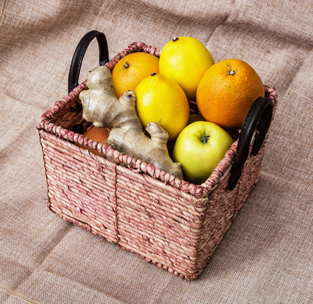 apples and oranges: Wicker basket with apples, oranges, lemons and ginger on the cloth background. Healthy food.