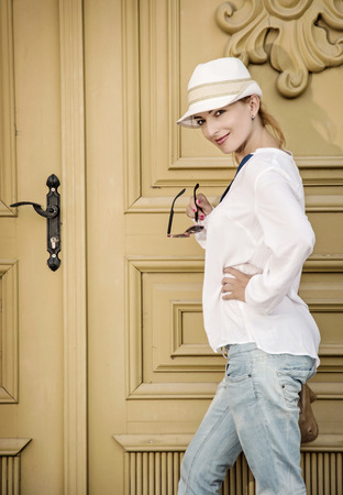 sunhat: Young caucasian woman with stylish sunhat posing in front of the old gate. Beauty and fashion.