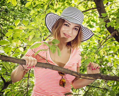 sunhat: Young positive caucasian woman with stylish sunhat posing on the tree. Beauty and nature.