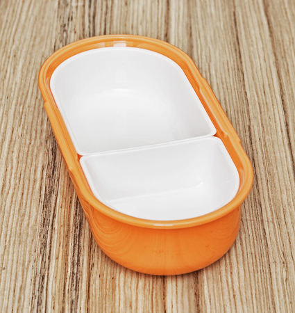 food storage: Orange folding plastic box for food storage on the wooden background. Kitchen equipment.