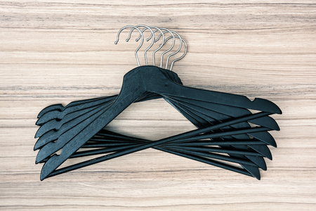 garderobe: Set of black coat hangers on the wooden background.