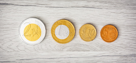 moneyed: Chocolate money on the wooden background. Euros and cents. European currency.
