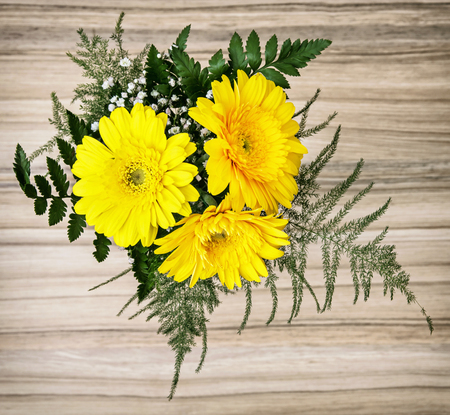 gerbera daisies: Bouquet of yellow gerbera daisies on the wooden background. Birthday gift.