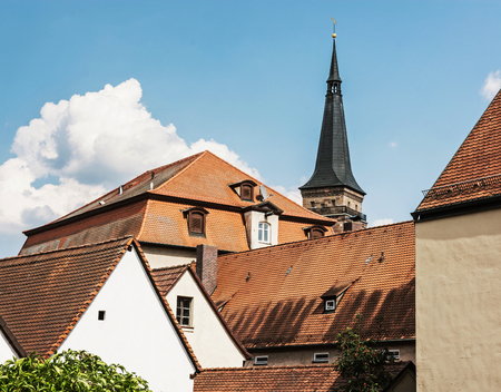 johannes: Red roofs and tower of church in Schwabach city, Bavaria, Germany. Clouds in blue sky. Travel destination. Stock Photo