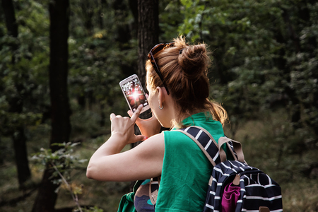 singleness: Young caucasian woman takes photo with smartphone in the forest. Tourism theme. Stock Photo