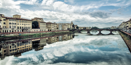 trinita: Old buildings and beautiful Ponte Santa Trinita mirrored in the river Arno, Florence, Tuscany, Italy. Dramatic cloudy sky. Travel destination.