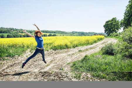 rappi: Joyful caucasian woman is jumping in rapeseed field. Beauty, fashion and nature. Vibrant colors.