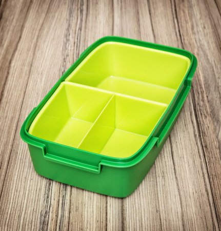 food storage: Green plastic box for food storage on the wooden background. Kitchen utensil.