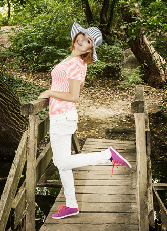 sunhat: Young cauciasian woman with sunhat posing on the wooden bridge. Beauty and nature.