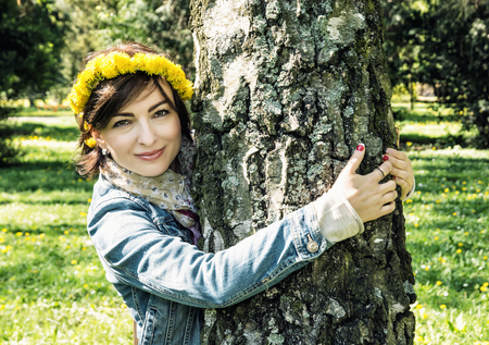 face in tree bark: Young romantic woman with wreath of dandelions on the head is hugging the birch in the park. Natural beauty. Stock Photo
