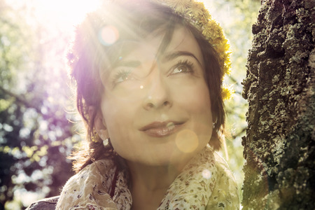 face in tree bark: Young romantic woman with wreath of dandelions on the head in sun rays is looking up. Natural beauty. Stock Photo
