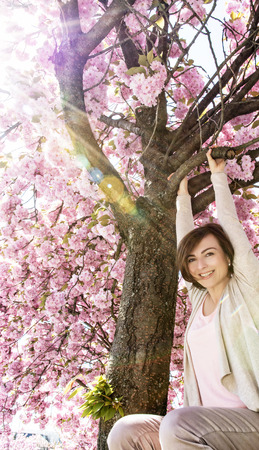 Happy young woman is hanging on the sakura tree with reflected sun rays. Beauty and nature. Stock Photo