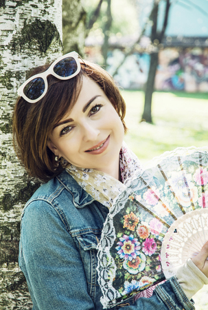 birch tree: Beautiful young woman with hand fan is leaning on the birch tree in the park. Beauty, fashion and nature.
