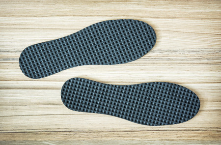 insoles: New orthopedic shoe insoles on the wooden background.