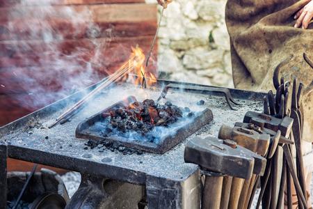 manufactory: Artistic blacksmith works in the historic blacksmith workshop. Horseshoe for good luck. Manufactory theme. Art production.