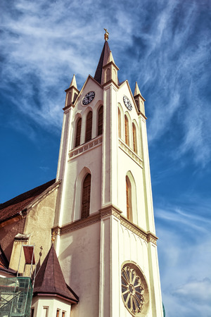 vertical composition: Big church in Keszthely, Hungary. Architectural theme. Vertical composition. Religious architecture. Blue sky. Franciscan church. Place of worship.