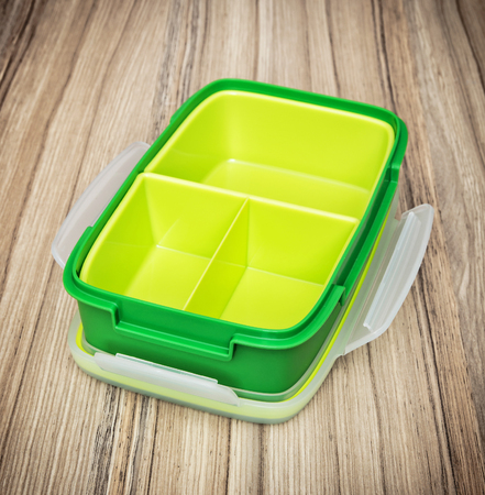 food storage: Green plastic box for food storage on the wooden background. Kitchen utensil. Close up photo.