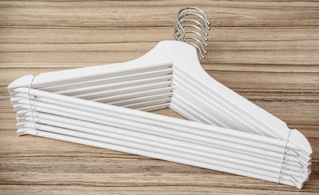 garderobe: Set of white coat hangers on the wooden background. Home related.
