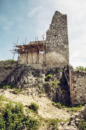 central europe: Ruins of Plavecky castle, Slovak republic, central Europe. Repair the castle, scaffold. Travel destination. Vertical composition. Stock Photo
