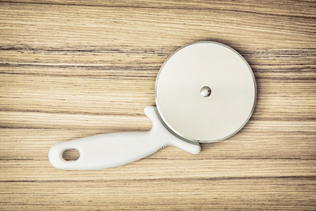 kitchen equipment: Pizza cutter on the wooden background. Kitchen equipment. Pizza slicer. Kitchen tool.