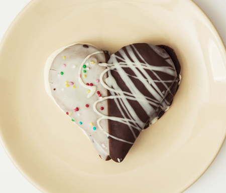 gingerbread heart: Tasty decorative gingerbread heart on the yellow plate. Sweet food. Tasty cookie.