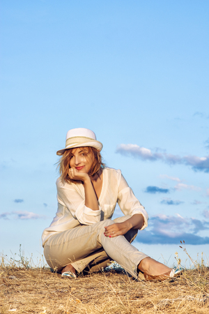 compostion: Pretty caucasian woman with stylish hat is sitting on dry grass by sunset with blue sky behind. Beauty and fashion. Vertical compostion. Seductive young woman.