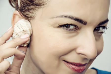 solter�a: mujer cauc�sica joven que escucha la concha. Retrato de detalle. Belleza y la moda. Mujer atractiva.