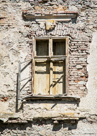 vandalize: Old damaged brick wall with window. House for demolition. Architectural element. Stock Photo