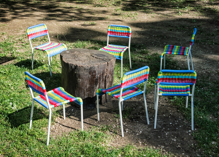 lawn party: Colorful chairs and wooden table on the lawn. Garden party. Light and shadow.